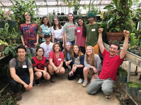 Group of undergraduate students gathered at a greenhouse.