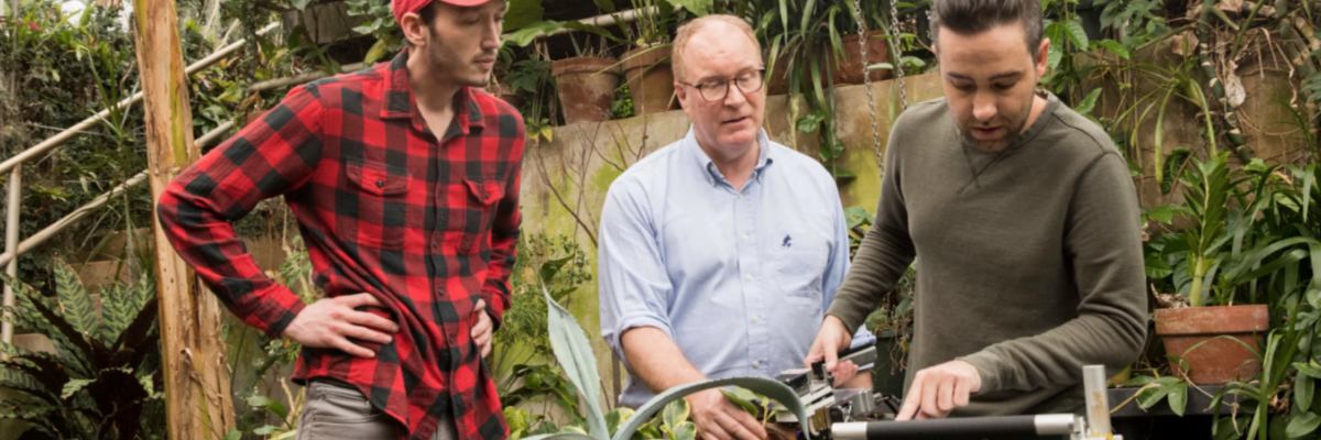 Graduate student Philip Bentz, professor James Leebens-Mack, and graduate student Rick Field use a carbon dioxide sensor on a plant in the horticulture greenhouses.